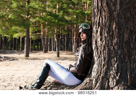 lonely woman in helmet of the pilot sits at a tree on the beach