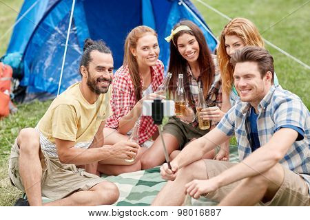 camping, travel, tourism, hike and people concept - happy friends with glass bottles drinking cider or beer and taking picture by smartphone on selfie stick at camping