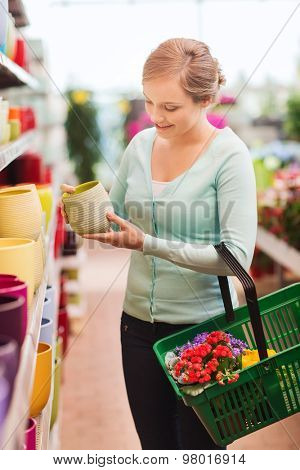 people, gardening, shopping, sale and consumerism concept - happy woman with basket buying flowers and choosing flowerpot at flower shop