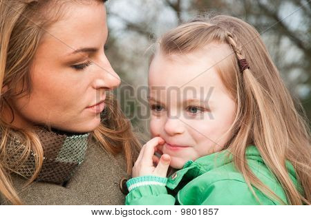 Puzzled Little Girl On Mother's Hands