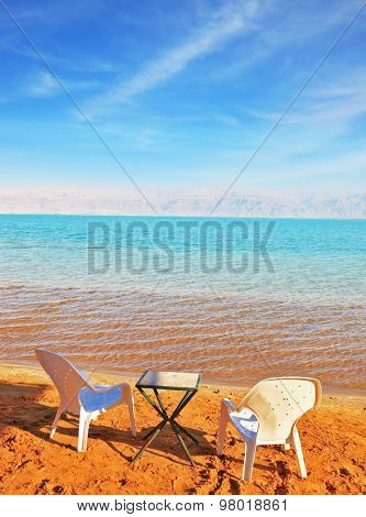 Beautiful sunny day at a beach resort. Dead Sea, the orange sand and beach chairs waiting for tourists