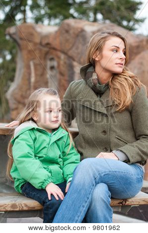 Mother And Daughter Resting On A Bench
