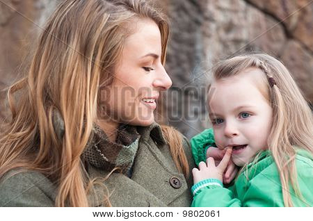Smiling Young Woman Holding Her Daughter