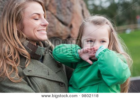 Happy Little Girl Covering Mouth With Hands Held By Her Mother