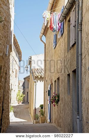 Narrow Street With Old Houses And Laundry In South Europe