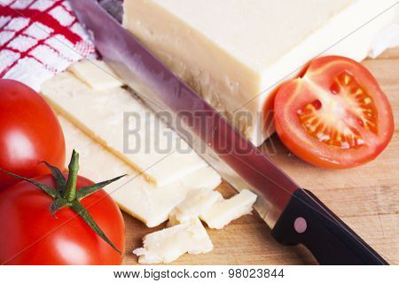 Tomatoes And Cheese With Knife On Chopping Board