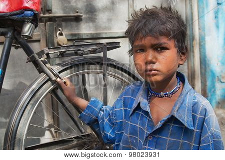 Portrait of unidentified boy with a bicycle at the street of Jodhpur, India.