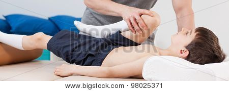 Physiotherapist Stretching Patient's Leg