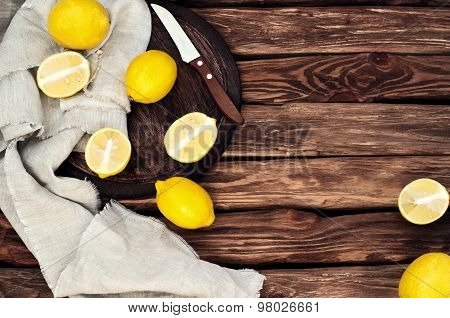 Scattered Yellow Lemons On The Old Wooden Background