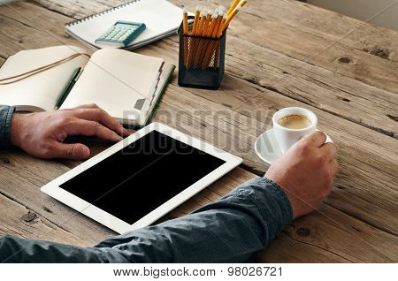 On The Wooden Table Is A White Tablet Computer