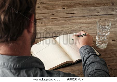 Hand Of Man Writing Something In Blank Notebook