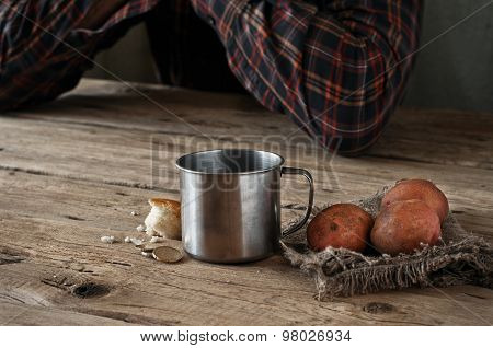 On The Wooden Table Is A Mug Of Water, A Slice Of Bread, Potatoes And A Few Euro Cents