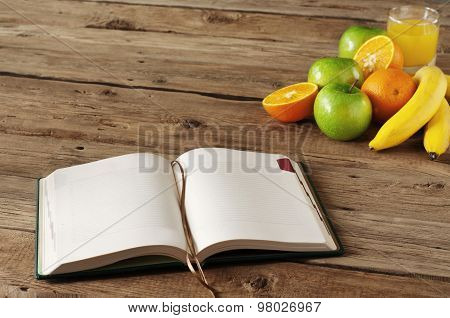Open Notebook On Wooden Table With Fruits And Orange Juice