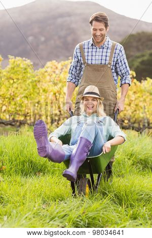 Portrait of a couple in dungarees pushing a wheelbarrow
