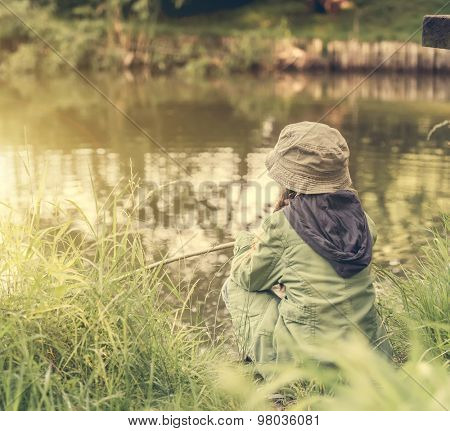 little fisher girl sitting on a river bank with a rod