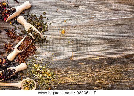 scented tea in spoons and scoops on wooden background