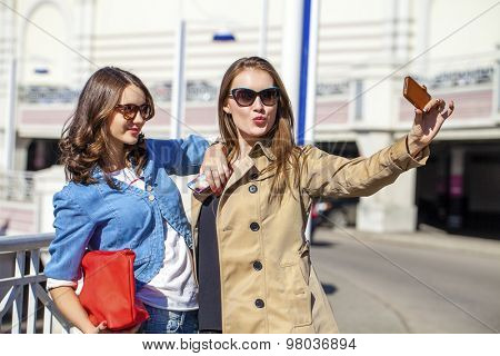 Two young beautiful girlfriends in sunglasses in the summer city