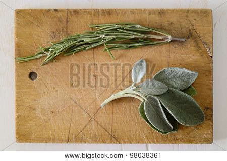 Two Fresh Green Mediterranean Herbs Rosemary Branch And Sage Leaves On A Brown Wood Cutting Board On