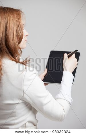 young woman writes with a stylus on a tablet