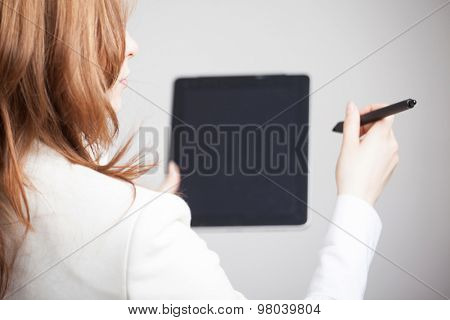 woman holding a tablet and black stylus