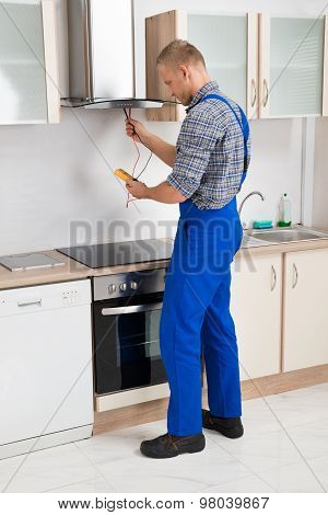 Worker Testing Kitchen Hood With Multimeter