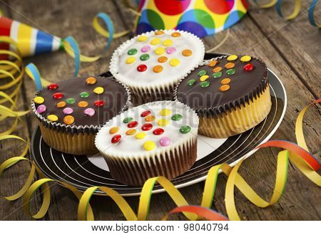 four cupcakes with dark and white chocolate icing and smarties on a plate, surrounded by streamers and party hats, tilted view