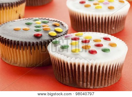 Cupcakes with white and dark chocolate icing and smarties