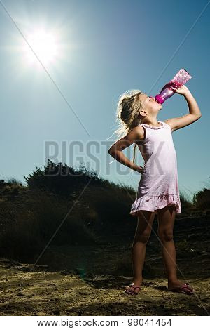 A Girl Standing In The Desert Sand Under The Hot Sun Drinking Water