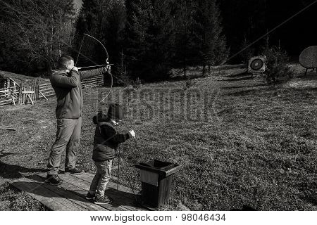 The father teaches his son to shoot a bow