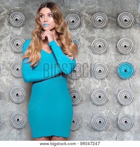 fashionable woman with long brown hair wearing blue dress standing against the wall