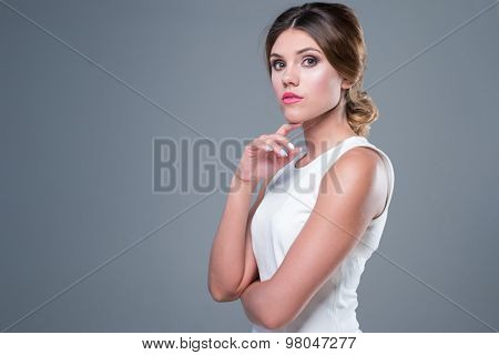 woman with brunette hair standing posing with white dress on grey