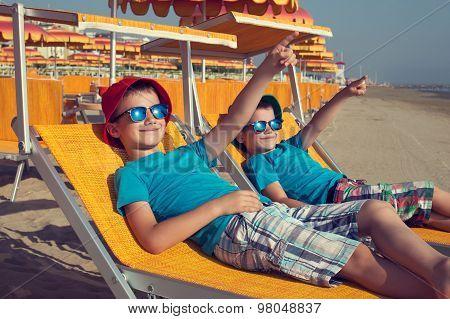 Little Boys Relax On Deckchair Showing Away