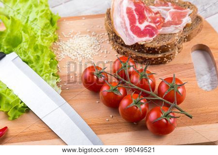 Healthy breakfast with tomato, toasts, meat and salad on wooden table
