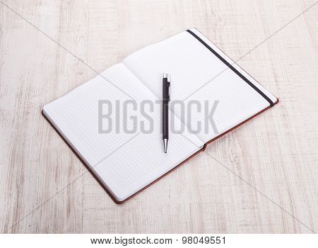 top view of open book with pen on wooden table.