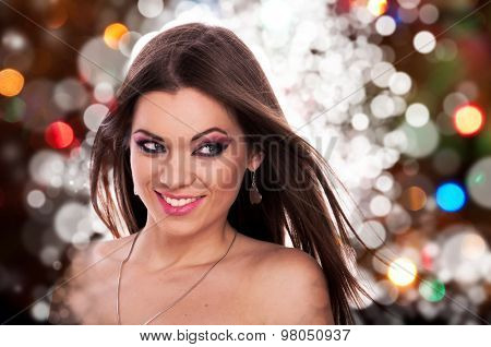 Beautiful young woman with fluttering hair posing on a background with colorful defocused lights