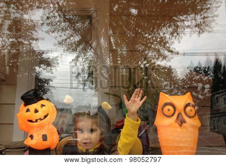 Authentic image of a toddler girl waving at a window in a Halloween costume  in the Instagram filtered style - soft focus