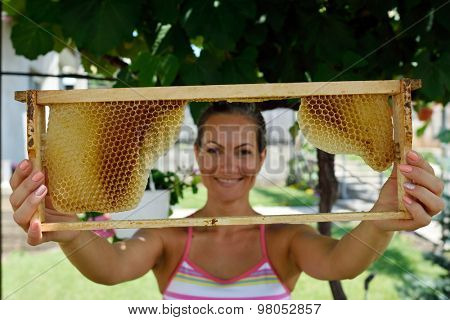 young smiling woman holding frame with honeycomb