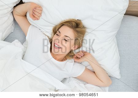 Woman Stretching Arms In Bed