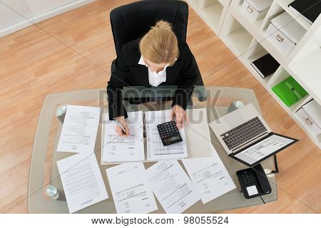 Businesswoman Calculating Invoices In Office