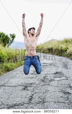 Shirtless muscular young man jumping for joy