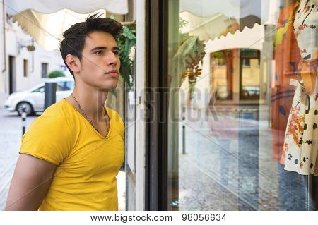Young Man Looking at Fashion Items in Shop Window