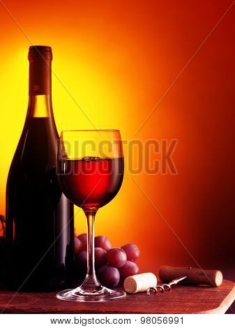Bottle and glass of red wine on dark red background. Filtered image: warm cross processed vintage effect.