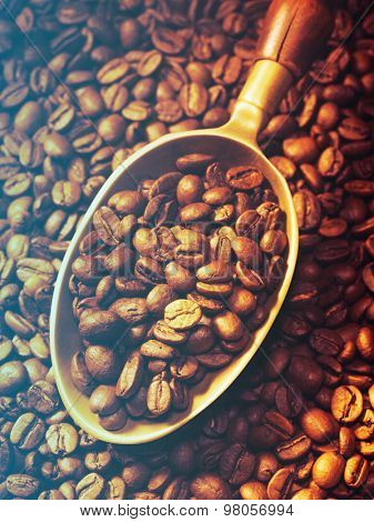 brass scoop with whole coffee beans on a coffee beans background.Filtered image: cool cross processed vintage effect.