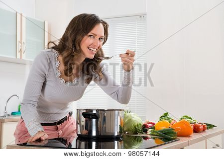 Woman Smiling While Tasting Meal In Kitchen