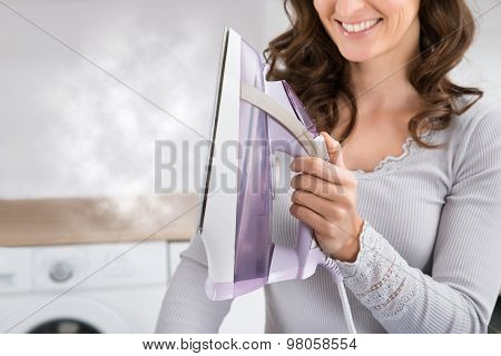 Close-up Of Woman With Steam Iron