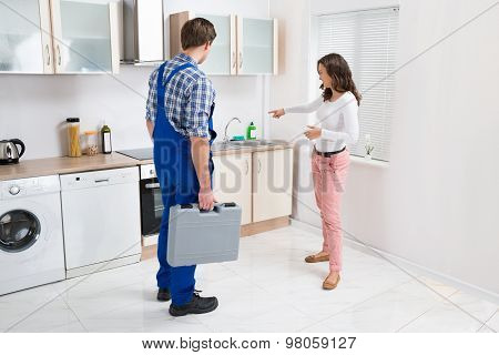 Woman Showing Damage In Sink To Plumber