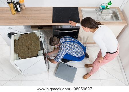 Woman Looking At The Repairman Repairing Dishwasher
