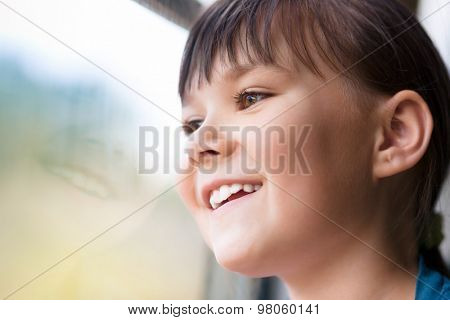 Happy girl is looking through window while sitting in train, closeup shoot