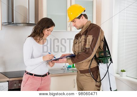 Woman Signing Document In Front Of Exterminator