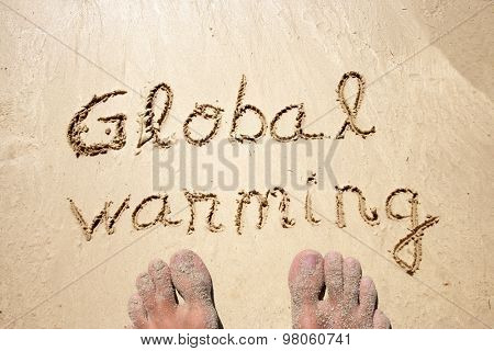 Concept or conceptual Global warming text handwritten in sand on a beach background with feet